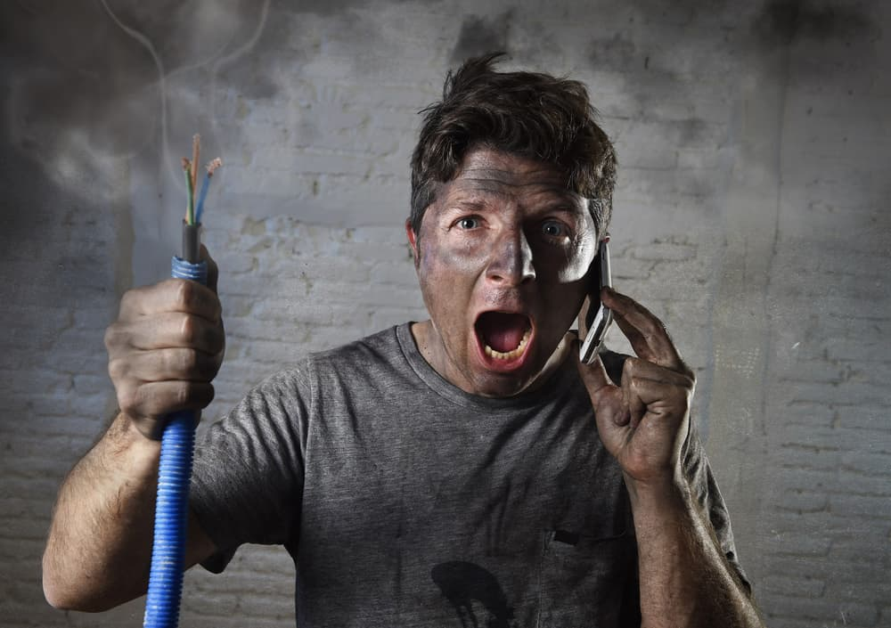 Young man holding electrical cable smoking after electrical accident with dirty burnt face in funny desperate expression calling for help.